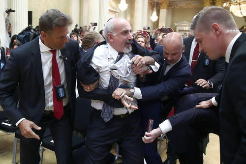 دستگیری یک مرد با پلاکارد انتقادی در نشست خبری روز دوشنبه ترامپ و پوتین در هلسینکی/ ایتارتاس و شینهوا