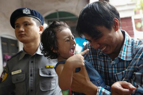 خبرنگار زندانی رویترز در حال بازی با دخترش در مقابل دادگاه در شهر یانگون میانمار