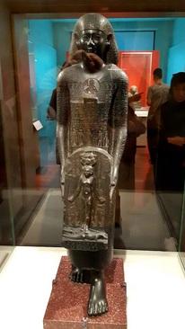 مجسمه شفابخش/ نئونتوپُلیس(مصر) قرن 4 پیش از میلاد/ سنگ بازالت/ الحاق به مجموعههای موزه لوور در 1898 میلادی/ مجسمه کاهن ناشناس، نصب شده احتمالا روی حوض به شکلی که آب روی مجسمه میریخته و سپس به داخل حوض سرازیر میشده، با کتیبۀ روی مجسمه با این مضمون:«کسی که از این آب بنوشد، باشد که همین قلبش و همین سینهاش با این حمایتهای جادویی محکم شود» آبی که همراه با خواندن این اوراد نوشیده میشد دوای
