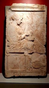 سنگ مزار با نام فیلیس/ جزیره تاسوس(یونان)، حدود 440-450 پیش میلاد/ مرمر تاسوس، حاصل از ماموریت کاوش امانوئل میلر،1865 میلادی/ سنگ مزار بزرگ با تصویر بانوی متوفی،«فیلیس، دختر کلئوکن» بر اساس کتیبۀ موجود بر ان. دختر جوان روی چهارپایه نشسته، با پیراهنی کوتاه و بالاپوش ضخیم و چیندار روی آن و جعبهای در دست راست او. بر اساس سبک اثر، مربوط به دورۀ خلق حاشیههای تزئینی معبد پارتنون در شهر آتن، کشف شده در سال 1862 در جزیره تاسوس(شمال یونان)، مقارن افزایش کاوشهای باستانشناسان فرانسوی در حوزۀ مدیترانه است.
