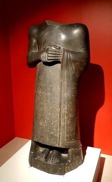 مجسمۀ گودِآ/ دوران نو-سومری، دوره حکمرانی گودِآ حدود 2120 پیش میلادی./ سنگ گابرو، کاوشهای ارنست دوسارزک،1881 میلادی/ گودِآ شاهزاده سومری، در حالت ایستاده و با دستهای به حالت دعا، بدون زیورآلات در هیئت پادشاهی با تقوا که دستور بازسازی معابد شهرش را داده بود. از کاووشهای ارنست دو سارزک در تللو که به کشف تمدن سومری و تاسیس دپارتمان ویژه برای آثار باستانی شرقی در موزۀ لوور در سال 1881 منجر شد.