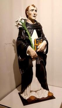 کارگاه خانوادۀ دلا روبیا، مجسمۀ دومینیک قدیس/ فلورانس(ایتالیا)، حدود 1520 میلادی./ گل پخته لعابدار و چند رنگ./ دومینیک قدیس با پوشش سفید و سیاه فرقه دومینیکن که خود در قرن سیزدهم میلادی تاسیس کرد و گل زنبق نماد این فرقه بود. کارگاه خانوادۀ دلا روبیا در قرون پانزدهم و شانزدهم میلادی نوآورییهایی در زمینۀ تولید مجسمههای یادبود از جنس گل پخته لعابدار داشت.