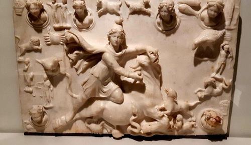 میترا در حال کشتن گاو نر/ صیدا، صیدون باستانی(لبنان)، اواخر قرن3 یا قرن 4 میلادی/ سنگ مرمر، اهدایی هانری دو بواژلن 1967 / ایزد ایرانی، میترا، در حال قربانی کردن گاو نر، عقرب که در اینجا نماد نیروهای شر است گاو را نیش میزند. یک سگ و یک مار از خون مغذی گاو نر مینوشند. در این نقش برجسته، نیم تنه های نمادین چهار فصل و ماه و خورشید و همچنین نشانه های 12 صورت فلکی آمده است. قربانی کردن گاو نر جایگاه مهمی در آئین میترا داشت. آئینی که توفیق فراوان در سرزمینهای تحت سیطرۀ روم کسب کرده است. نمادهای موجود در این اثر بیانگر تولد دوبارۀ طبیعت و چرخۀ زمان هستند.