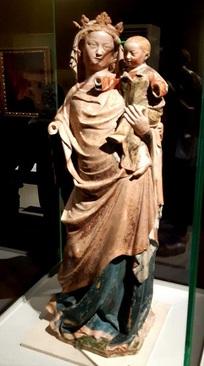مریم عذرا و کودک/ ناحیه لورن فرانسه، حدود 1330-1320 میلادی/ سنگ آهک چندرنگ، اهدایی انجمن دوستدارانلوور،1979 میلادی./ مجسمه مریم عذرا که مسیح کودک را در آغوش دارد و قرار بوده در یک کلیسا نصب شود. وضعیت پیکر مریم عذرا، که پسرش را در آغوش گرفته، به هنرمند اجازه داده بر پیوند عاطفی آنها تاکید کند. این گونه خاص نمایش حضرت مریم و فرزندش از ویژگیهای مجسمهسازی گوتیک(قرن 13 تا اوائل قرن 16 میلادی) است.