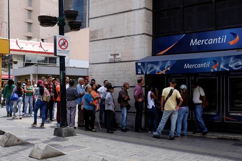 صف بستن مردم مقابل یک دستگاه خودپرداز بانکی برای بیرون کشیدن پول ها و خرید مایحتاج و سوخت/ کاراکاس