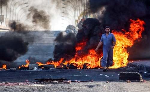 بستن خیابان با آتش زدن تایر از سوی معترضان به دولت در شهر بصره در جنوب عراق / خبرگزاری فرانسه