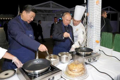 روسای جمهوری روسیه و چین در حال درست کردن پنکیک روسی در حاشیه دیدارشان از یک نمایشگاه اقتصادی در ولادی وستک روسیه/ ایتارتاس
