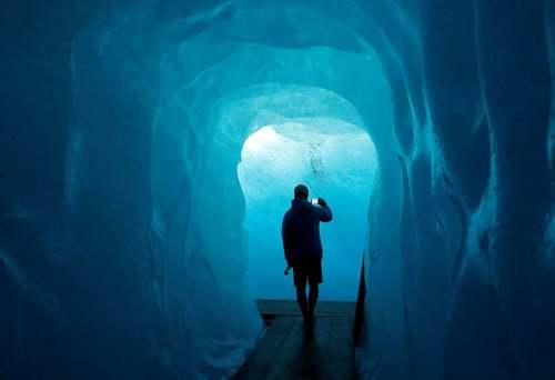یک گردشگر در حال بازدید از یک غار یخی در