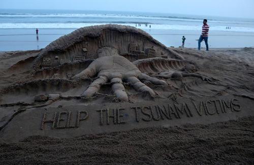 یک هنرمند هندی در همدردی با قربانیان فاجعه زلزله و سونامی در اندونزی یک اثر شنی در ساحل