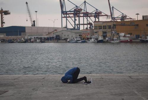 نماز خواندن یک پناهجوی آفریقایی پس از رسیدن به جزیره مالاگا اسپانیا