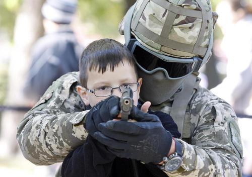 سرباز گارد مرزی اوکراین در حال آموزش نحوه تیراندازی به یک پسربچه اوکراینی در نمایشگاه