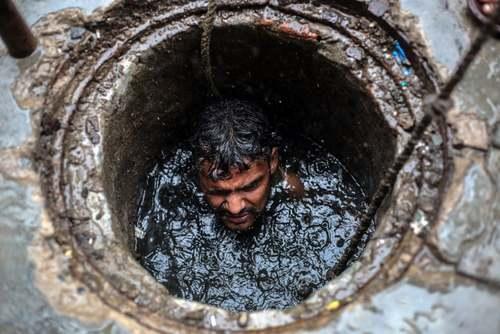 کارگر هندی بدون هیچ وسیله ایمنی برای پاکسازی داخل چاه فاضلاب شهری در شهر قاضی آباد رفته است. آمارها نشان دهنده مرگ یک کارگر در هر 5 روز در عملیات چاهروبی در هند است./EPA