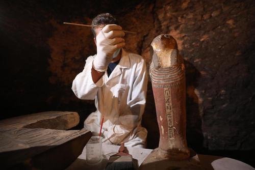 یک باستان شناس مصری در حال کار در یک مقبره تازه کشف شده فراعنه در صحرای جیزه/ خبرگزاری آلمان