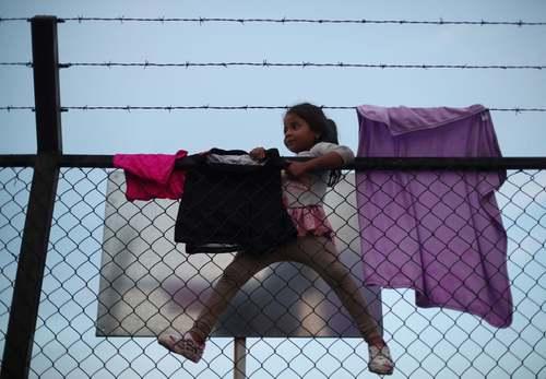 بالا رفتن دختر 5 ساله مهاجر هندوراسی از دیوار مرزی آمریکا و مکزیک/ رویترز