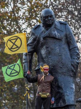 تظاهرات حامیان محیط زیست در لندن. یک فعال محیط زیست در کنار مجسمه وینستون چرچیل در مقابل پارلمان بریتانیا در