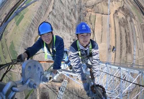 کارگران در حال کار روی دکل انتقال برق/ چین