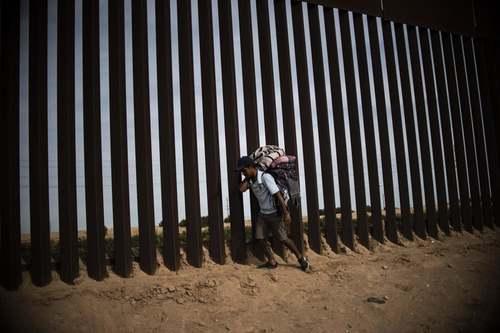 یک مهاجر از کشورهای آمریکای مرکزی در حصار مرزی بین مکزیک و ایالت کالیفرنیا آمریکا/ خبرگزاری فرانسه