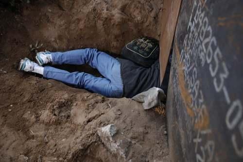 کندن زمین از زیر دیوار مرزی از سوی یک مهاجر هندوراسی برای عبور به آن سوی دیوار مرزی مکزیک و ایالات متحده آمریکا/ آسوشیتدپرس