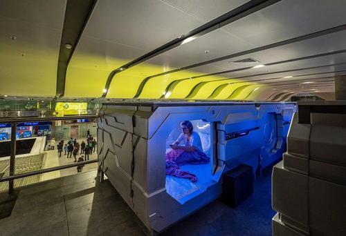 یک زن در اتاق خواب هتل کپسول- فضایی در فرودگاه بینالمللی