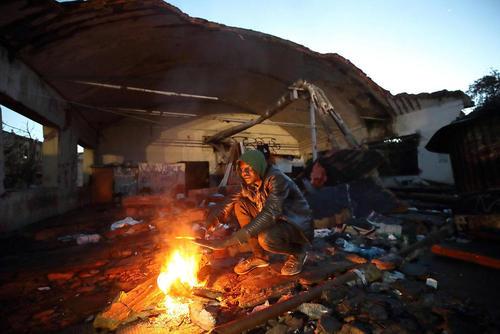 گرم شدن یک پناهجو با آتش در یک مجتمع صنعتی مخروبه در شهر رم ایتالیا