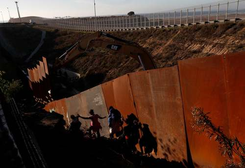 تلاش مهاجران برای عبور از دیوار مرزی بین مکزیک و ایالات متحده / رویترز