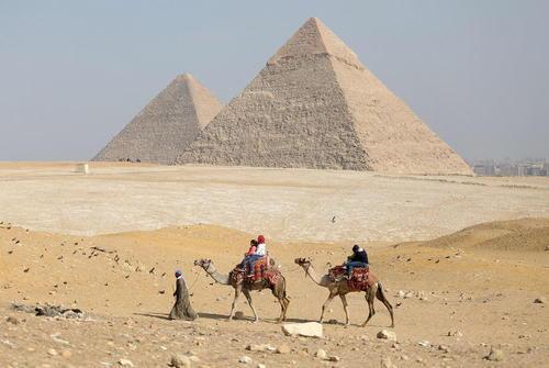 بازدید گردشگران بر روی شتر از اهرام ثلاثه مصر