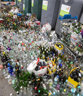 گذاشتن بطریهای مصرف شده برای بازیافت در مقابل یک مرکز جمعآوری وبازیافت بطریها در