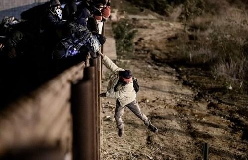 تلاش یک مهاجر برای عبور از مانع مرزی مکزیک و ایالات متحده آمریکا/ خبرگزاری فرانسه