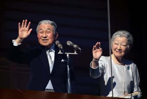 امپراتور ژاپن و همسرش در حال پاسخ دادن به ابراز احساسات مردمی در دیدار سال نو مردم از کاخ امپراتوری از پشت شیشه ضد گلوله محوطه بالکن قصر/EPA