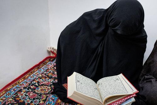یکی از زنان روستای بُجد قران می خواند. جلسات ختم قرآن از معدود تفریحات زنان روستاست