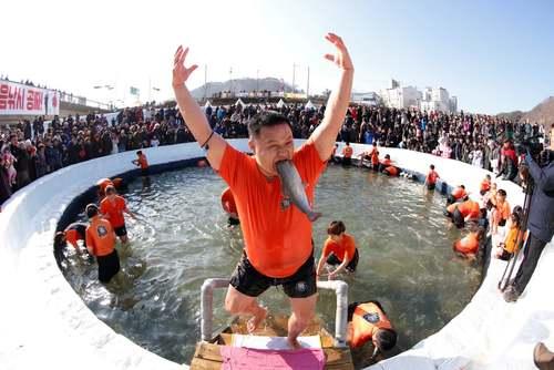شادمانی یک مرد کره ای از گرفتن یک ماهی با دست در جریان جشنواره یخ در