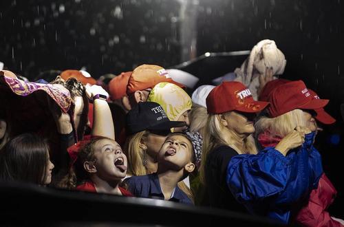 کودکان در حال خوردن قطرات باران به هنگام انتظار برای رسیدن هواپیمای حامل دونالد ترامپ و همسر و پسر کوچکش به فرودگاه بینالمللی شهر
