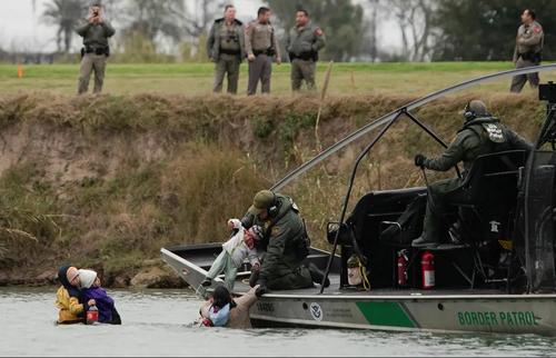 نیروهای گارد مرزی ایالات متحده آمریکا در حال نجات مهاجران غیرقانونی در رودخانه مرزی بین آمریکا و مکزیک/ رویترز