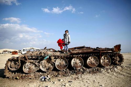 عکس یادگاری دختر 11 ساله سوری روی یک تانک تخریب شده در شمال حلب و در منطقه مرزی سوریه و ترکیه/ خبرگزاری فرانسه