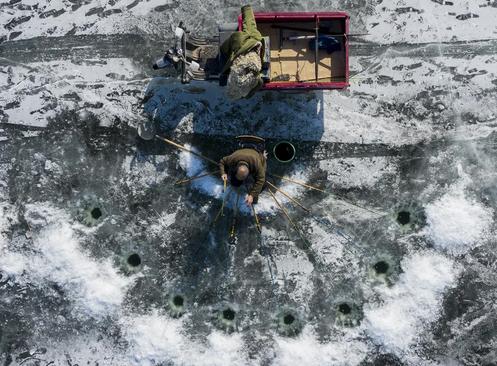 ماهیگیری در رودخانهای یخزده در شهر پکن چین