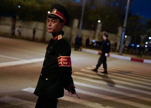 ماموران پلیس شهر هانوی ویتنام در انتظار عبور کاروان خودرویی حامل