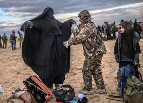 نیروهای کرد سوری تحت حمایت آمریکا در حال بازرسی بدنی افرادی که از مناطق تحت کنترل داعش در استان