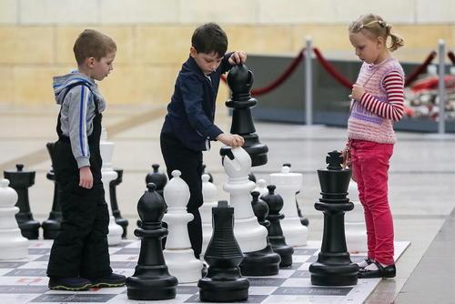 بازی کودکان روی یک صفحه بزرگ شطرنج در حاشیه برگزاری یک
