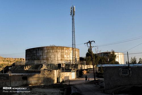 زنی با کودک خود در حال عبور از نزدیکی تانک بزرگ آب در محله سر برج شهر مسجد سلیمان هستند. این تانک آب در زمان جنگ ایران و عراق مورد اصابت موشک جنگنده های رژیم بعثی قرار گرفته بود و از آب آن بسیاری از خانه های پایین دست این منطقه تخریب و ویران شده بود.