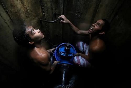ادامه مشکل قطعی آب در شهر کاراکاس ونزوئلا. دو پسر نوجوان در حال جمعآوری آب نوشیدنی از یک چاه زیرزمینی/ رویترز