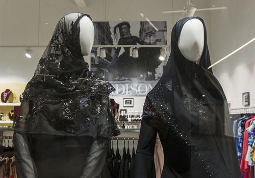 گذاشتن دو مانکن با حجاب در ویترین یک بوتیک لباس فروشی در شهر