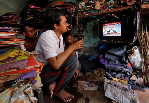 تماشای سخنرانی زنده نخست وزیر هندوستان خطاب به مردم هند در یک مغازه در شهر کلکته/ رویترز
