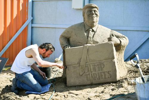 هنرمند بریتانیایی در حال کار روی مجسمه شنی دونالد ترامپ/PA