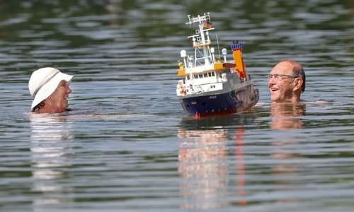 موج گرمای کمسابقه در اروپا. شنای یک زوج در دریاچه در شهر