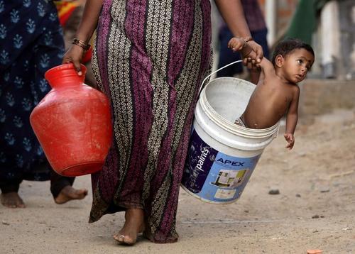 مادر هندی در صف دریافت آب از تانکر در حومه شهر