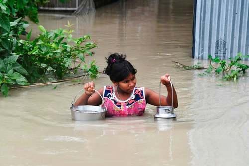 انتقال آب نوشیدنی در سیلاب ناشی از بارشهای موسمی در یک روستا در هندوستان/ گتی ایمجز