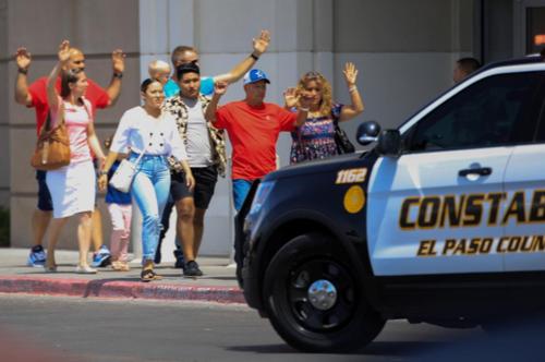 خریداران  به حالت تسلیم و با دستهای بالا رفته، از مرکز خرید الپاسو خارج میشوند/ رویترز