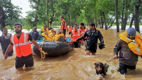 ماموران امداد و نجات در حال انتقال مردم از مناطق سیل زده/ نیوز نیشن