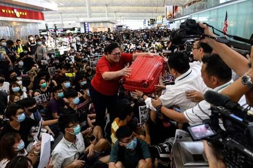 تلاش یک مسافر در فرودگاه بینالمللی هنگکنگ برای رساندن چمدانش به  کارکنان فرودگاه و عبور از ازدحام اعتصاب کنندگان/ خبرگزاری فرانسه و رویترز