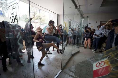 معترضان خشمگین در حال شکستن در شیشهای ورودی ساختمان دادستانی کل مکزیک در شهر
